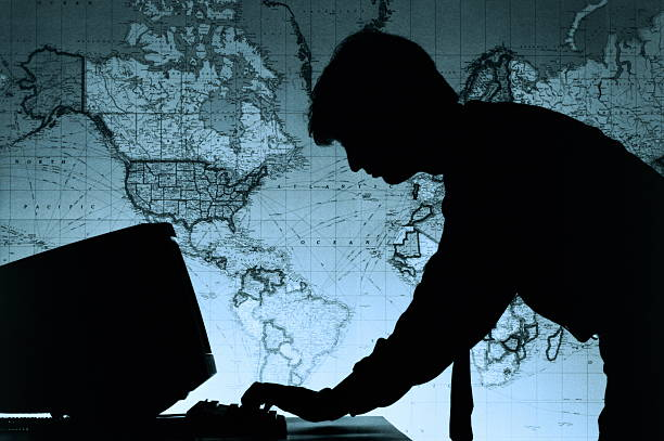 Male executive using computer,world map in background,silhouette (B&W)