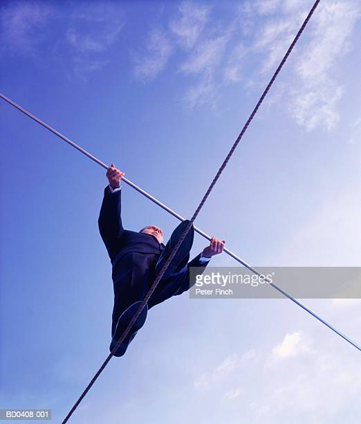 Male executive walking on tightrope, upward view