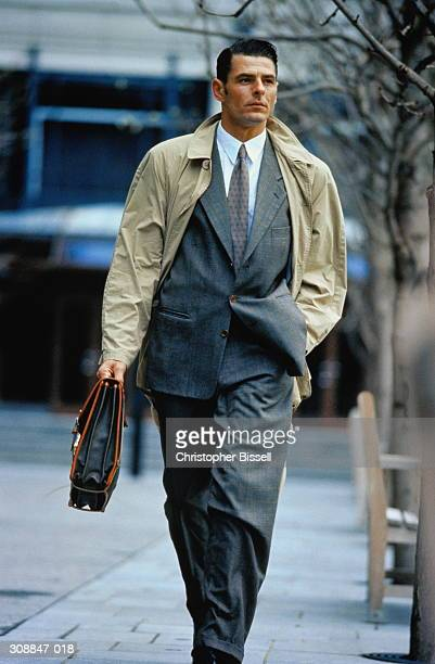 male executive with briefcase walking down street,outdoors - トレンチコート ストックフォトと画像