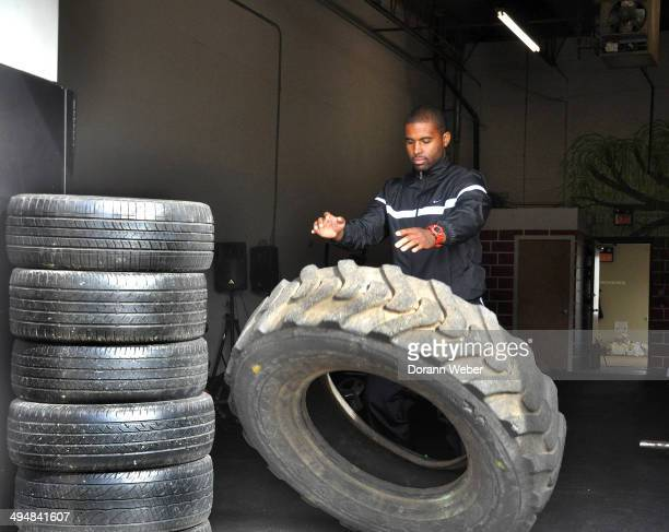Male exercises and strength trains with truck tires