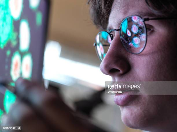 male expert examining coronavirus cells on computer monitor in laboratory - epidemiology stock pictures, royalty-free photos & images