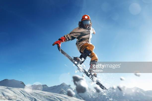 Male extreme freestyle snowboarder jump