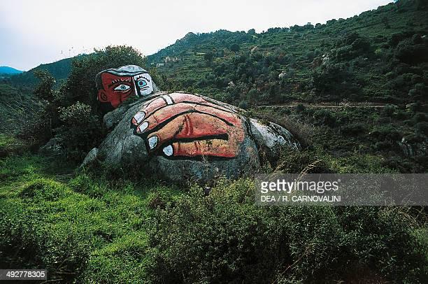 Male face and hand mural on a stone near Orgosolo Barbagia Ollolai Sardinia Italy
