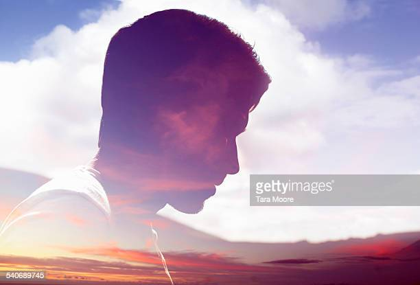 Male face silhouetted in sky