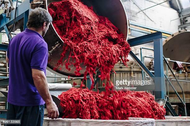 Male factory worker dyeing wool in woollen mill