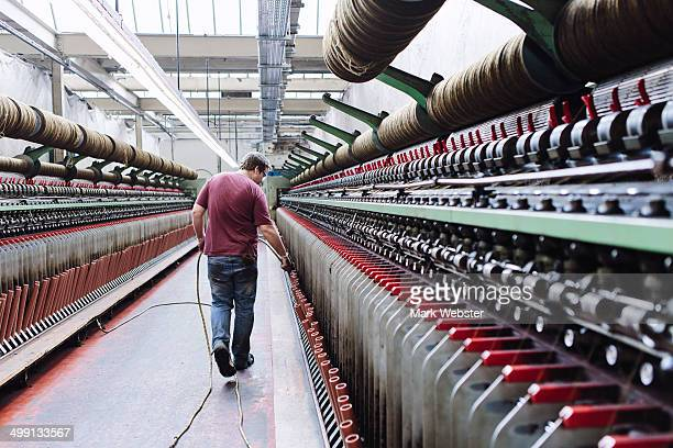 Male factory worker monitoring weaving machines in woollen mill