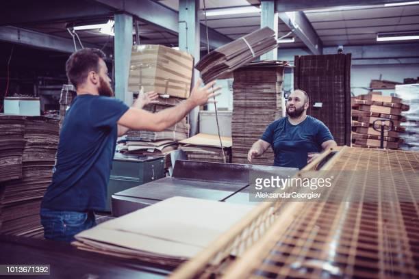männliche arbeiter kartonage paletten nach einander zu werfen - wurf oder sprungdisziplin herren stock-fotos und bilder