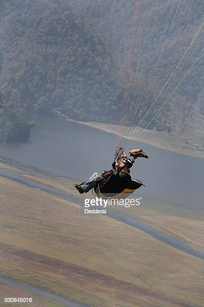 A male falconer flying a paraglider with his Egyptian vulture (Neophron percnopterus)