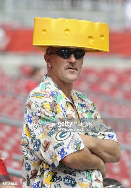 Male fan of Green Bay Packers wears cheese on his head as he watches warmups before play against the Tampa Bay Buccaneers at Raymond James Stadium on...