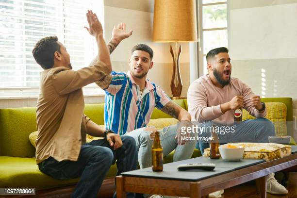 Male fans are enjoying soccer match at home