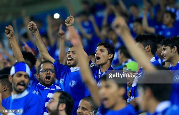 Male fans of al-Hilal FC cheer for their team ahead of the AFC Champions League play-off football match between Saudi's al-Ahli and al-Hilal at King...