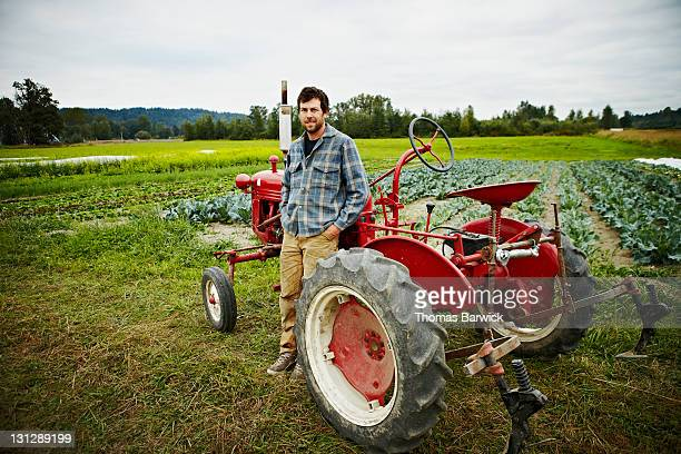 Male farmer leaning on tractor in front of field