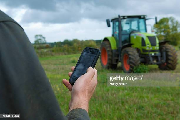 Male farmers hand holding up smartphone in field
