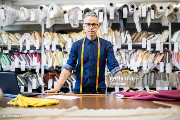 male fashion designer standing at workbench - fashion designer stock photos and pictures