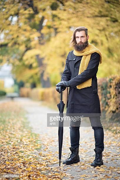 Homme Fashion, couleurs de l'automne, homme avec barbe et parasol
