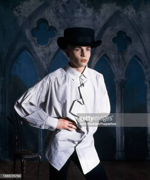 Male fashion model wear an outfit by John Galliano comprising a striped shirt with blouson sleeves and a concertinaed ruffle down the front and a...