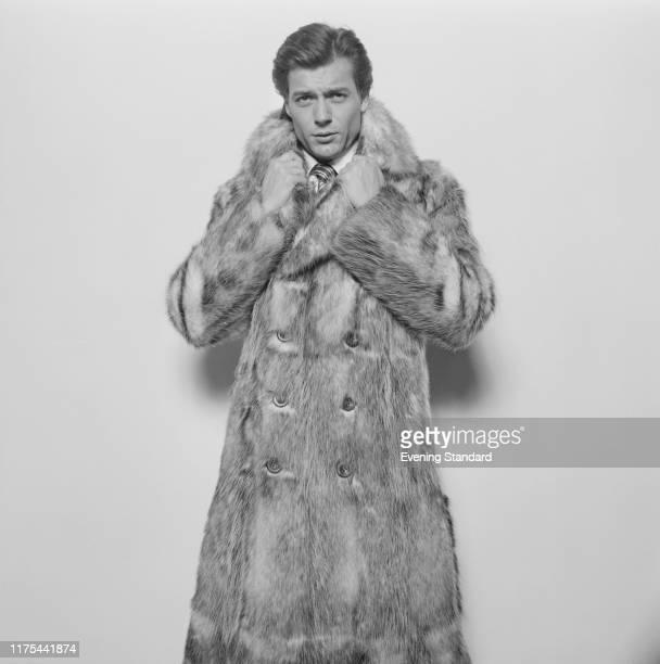 A male fashion model wearing long fur coat UK 20th December 1976