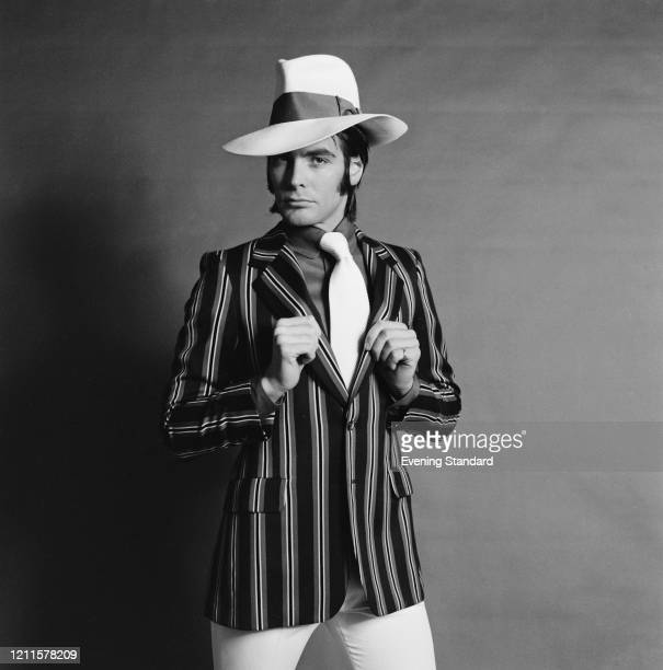A male fashion model wears a striped blazer with shirt white tie and fedora hat 20th January 1971