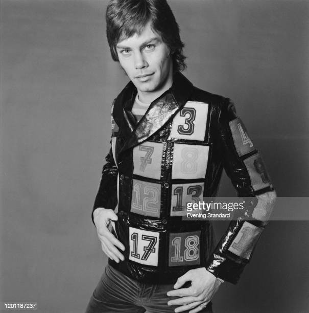 Male fashion model wears a vinyl double breasted jacket with sewn on number patches, 10th March 1971.