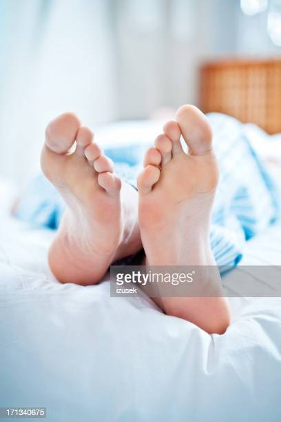 Male feet in bed