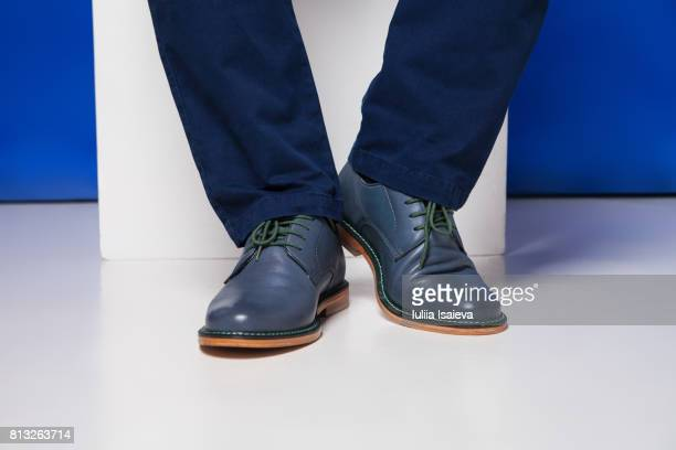 Male feet in shoes on studio background