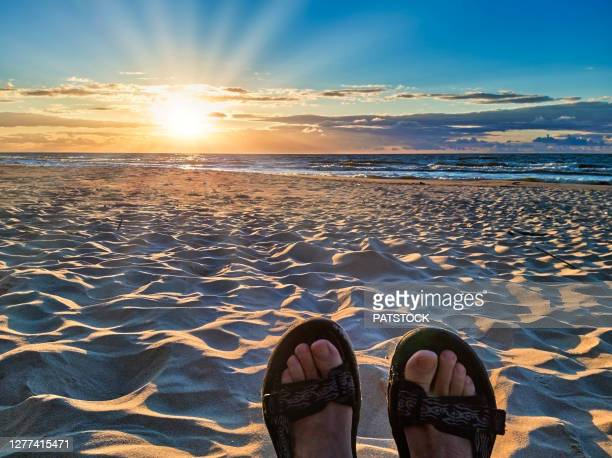 male feet wearing sandals against sunset at sea beach. - poland stock pictures, royalty-free photos & images