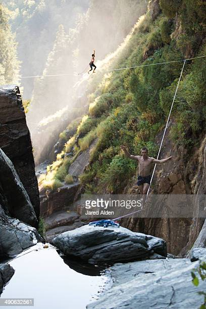 Male & female highliners simultaneously walking a two-way highline