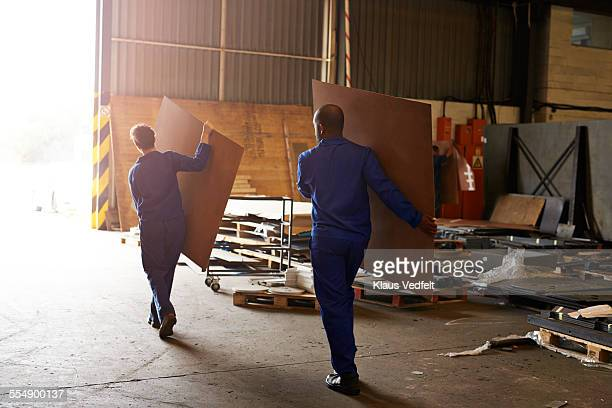 Male& female steel workers carrying plywood