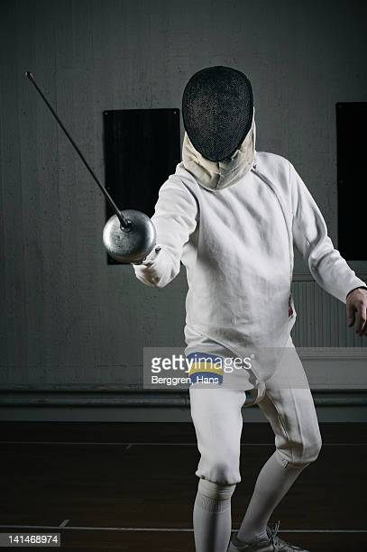 Male fencer in sports hall