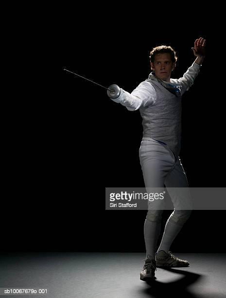 masculino esgrimista praticando, foto de estúdio - esgrima esporte de combate - fotografias e filmes do acervo