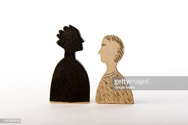 Male figures face to face, one black, one white