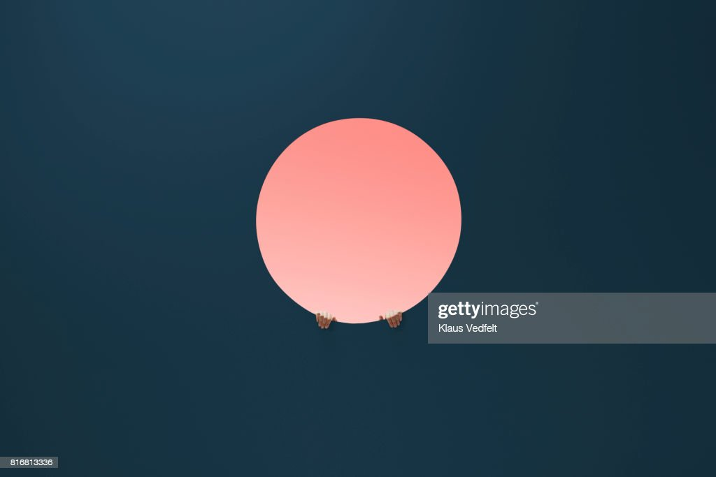 Male fingertips holding on to edge of round opening in coloured wall : Foto stock
