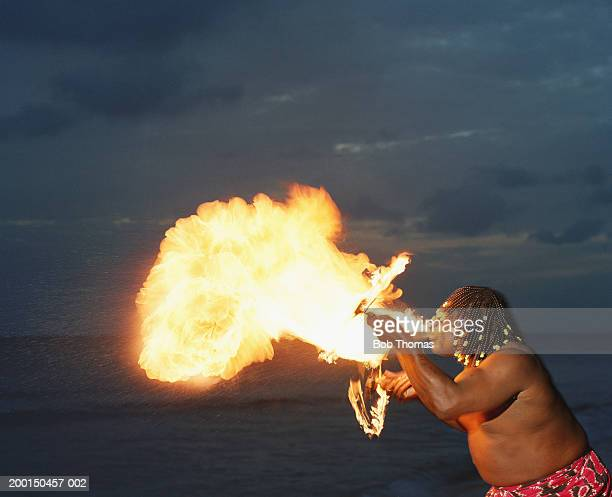 Male fire eater blowing flames from mouth, on beach, dusk
