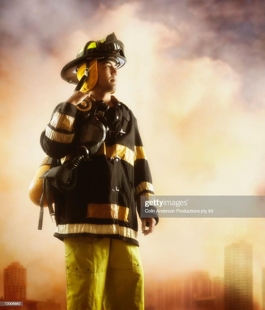 Male fire fighter with smoky background : Stock Photo