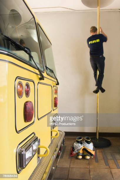 Male firefighter sliding down pole
