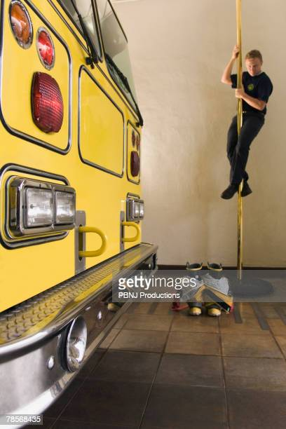 male firefighter sliding down pole - fire station - fotografias e filmes do acervo