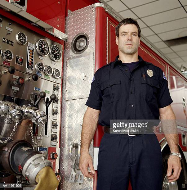 male firefighter standing beside firetruck, portrait - image stock pictures, royalty-free photos & images