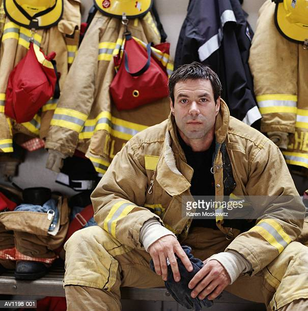 male firefighter wearing protective clothing, sitting - fire protection suit - fotografias e filmes do acervo