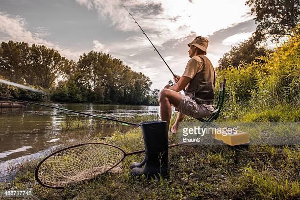 Männliche Angler Angeln im Fluss in den Tag.