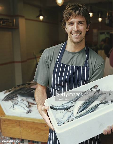 Male fishmonger holding box of mackerel, smiling, portrait