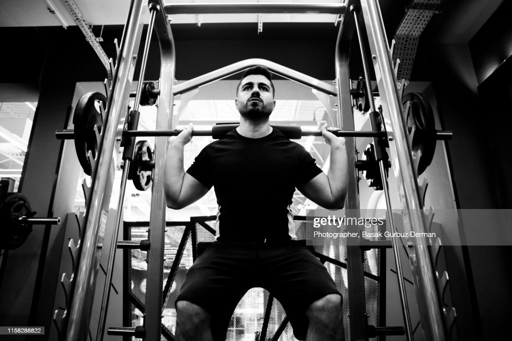 Male fitness athlete in the gym performing squats on Smith machine : Stock Photo
