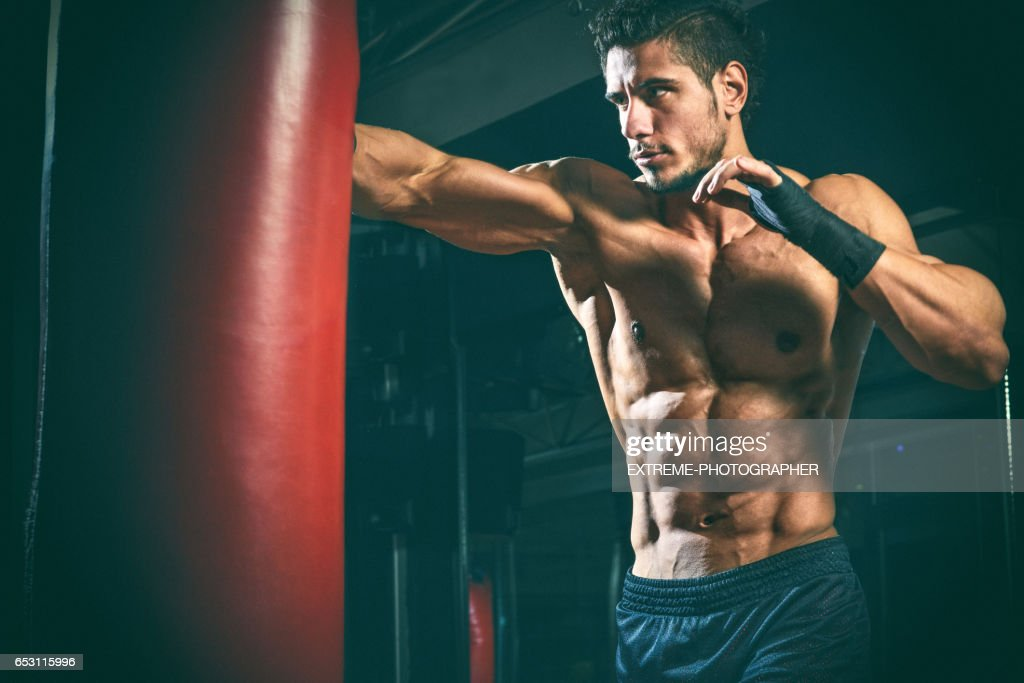 Male fitness athlete punching the bag : Stock Photo