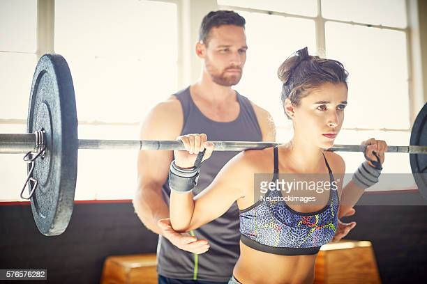 Male fitness instructor assisting female customer in lifting bar