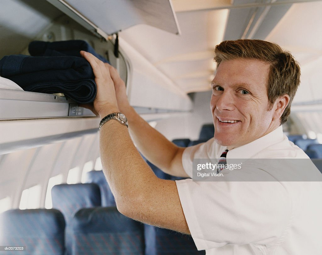 Male Flight Attendant Placing Objects in an Over Head Locker on a Plane : Stock Photo