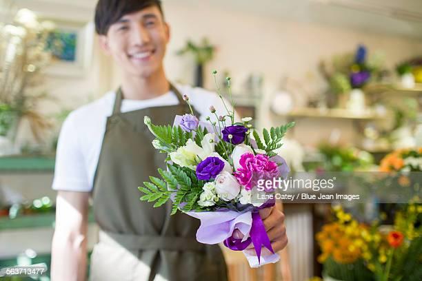 Male florist holding flower bouquet