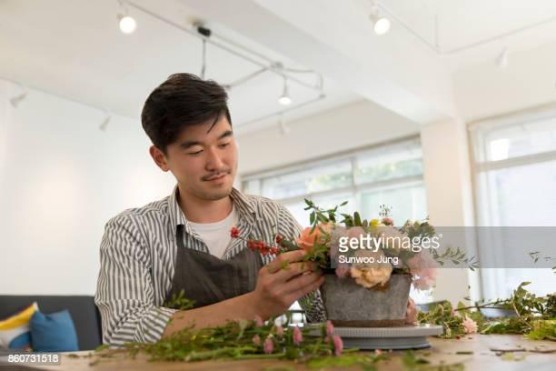 male florist making bouquet at flower arranging workshop - genderblend stockfoto's en -beelden