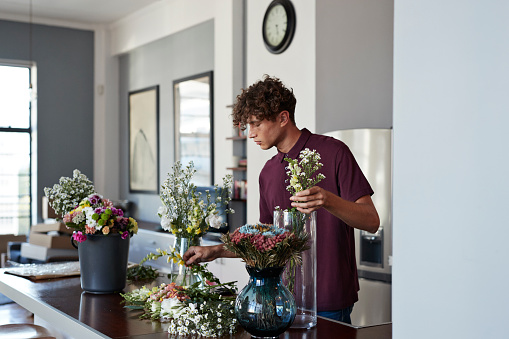 Male florist organising flowers for customer from home - gettyimageskorea