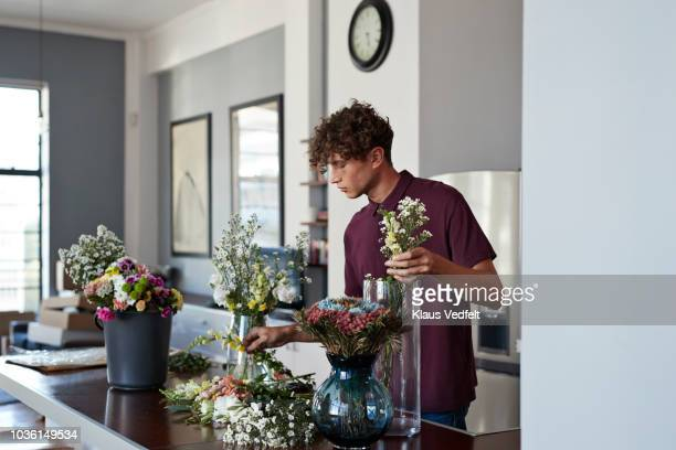 male florist organising flowers for customer from home - renovierung themengebiet stock-fotos und bilder