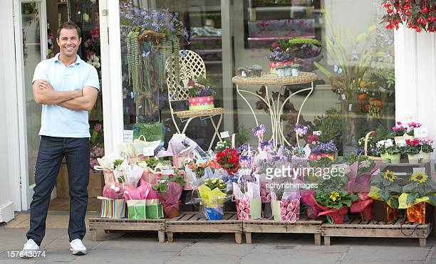 Florista hombre de pie fuera de tienda