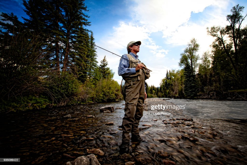 A male fly fisherman standing near a stream ready to fish : Stock Photo